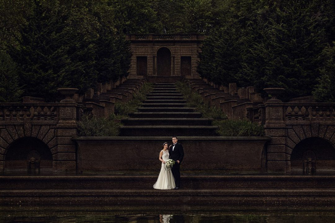 Wedding photographer Houston in Meridian Park during a destination wedding. Bride and Groom are standing in front of a 13 tiered waterfall.